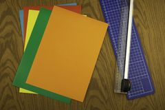 Paper cutter and color origami paper on a wooden table stock photo
