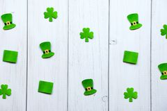 Paper decorations in form of leprechaun hat, flags and shamrock leaves on a gray wooden background. Happy St Patrick`s Day. Craft paper decorations in form of stock photos