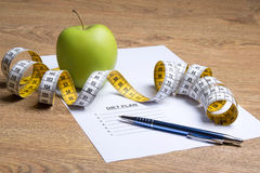 Paper with diet plan, apple and measure tape on table Royalty Free Stock Photos