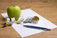 Paper with diet plan, pen, apple and measure tape on table Royalty Free Stock Image