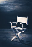 Paper director chair on a blueish grey background Stock Photos