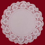 Paper doily lacy background, over red Royalty Free Stock Image