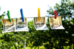 Paper dollars are drying on rope Stock Photos