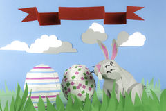 Paper Easter Bunny. Rabbit made of paper in a happy paper environment and a ribbon with space for text Royalty Free Stock Image
