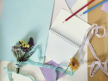 Paper, empty notebook, small bouquet, pencils on the table royalty free stock photo