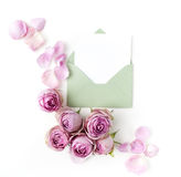 Paper envelop with white card and pink roses. Flat lay, top view Stock Images