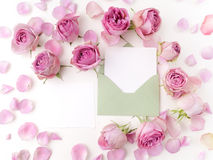 Paper envelop with white card and pink roses. Flat lay, top view Stock Photos