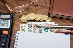 Paper with euro money, pen, calculator on table. Blank paper with euro money, pen, calculator on table Royalty Free Stock Image