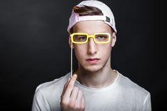 Paper eye glasses. Paper eyeglasses hand made crafts, accessories cardboard attributes on sticks for a professional photo shoot. Young man holding vision in his royalty free stock image