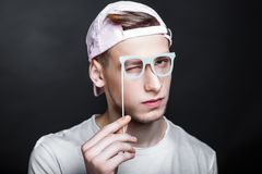 Paper eye glasses. Paper eyeglasses hand made crafts, accessories cardboard attributes on sticks for a professional photo shoot. Young man holding vision in his stock photos