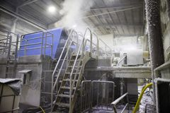 The paper factory. Industrial machinery for converting cellulose into a sheet of paper stock photography