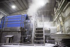 The paper factory. Industrial machinery for converting cellulose into a sheet of paper royalty free stock photo