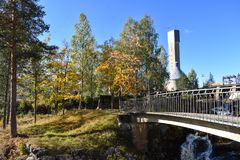 Paper factory`s tower, bridge and trees in autumn