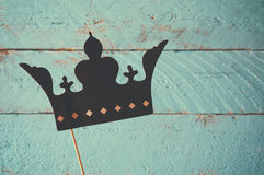 Paper fake crown in sticks. In front of wooden background. vintage filtered image Royalty Free Stock Photos