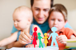 Paper family. Young father with his two kids holding figures of multicolored paper family Stock Photos