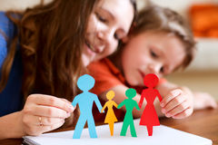 Paper family. Young mother and her son holding figures of multicolored paper family Stock Images