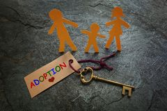 Paper family gold Adoption key. Paper family of three with gold key and colorful Adoption tag Royalty Free Stock Image