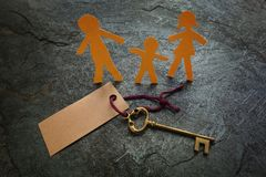 Paper family and gold key. Paper family of three with gold key and blank tag with copyspace Stock Photo
