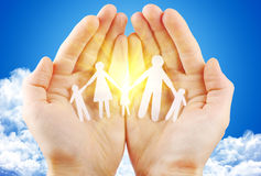 Paper family in hand. Sun and blue sky with copyspace showing freedom or solar power concept Royalty Free Stock Images