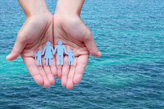 Paper family in hands on blue sea background welfare concept.  Royalty Free Stock Photography
