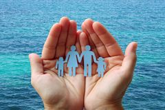 Paper family in hands on blue sea background welfare concept.  stock image