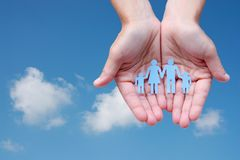 Paper family in hands on blue sky background welfare concept.  Stock Photos