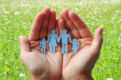 Paper family in hands on green meadow background welfare concept.  Stock Image