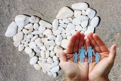 Paper family in hands with a heart of white stones in background welfare concept.  Stock Photography