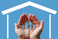 Paper family in hands with home on blue background welfare concept.  royalty free stock images