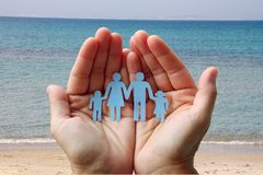 Paper family in hands on sea beach background welfare concept.  royalty free stock photo