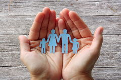 Paper family in hands on wooden background welfare concept.  stock image