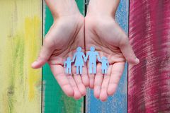 Paper family in hands on wooden coloured background welfare concept.  stock photo
