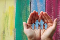 Paper family in hands on wooden coloured background welfare concept.  stock images