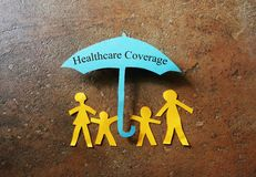 Paper family heathcare coverage. Paper family of four under a  Healthcare Coverage umbrella Royalty Free Stock Image
