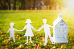 Paper family holds hands and house. Family and house concept. On background of green grass on bright sunny day, mom, dad and son Stock Photo