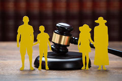 Paper Family With Mallet On Table In Courtroom. Closeup of paper family with mallet on table in courtroom royalty free stock photography