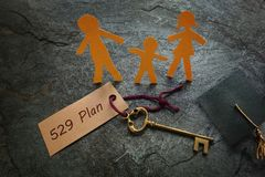 Paper family with 529 Plan gold key. Paper family of three with 529 Plan gold key --  college education savings concept Royalty Free Stock Photos