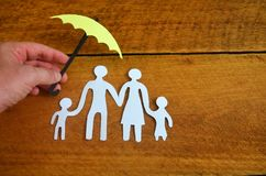 Paper family protected by an umbrella. Paper family protect by an umbrella in a wooden background Royalty Free Stock Photo