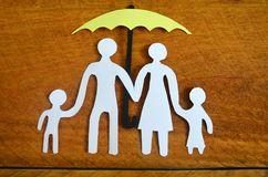 Paper family protected by an umbrella. Paper family protect by an umbrella in a wooden background Stock Photo
