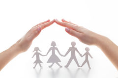 Paper family under hands in gesture of protection. Stock Photography