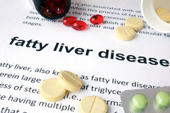 Paper with fatty liver disease and pills. Stock Images
