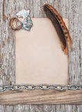 Paper, feather, seashells and metal chain on the old wood Stock Image