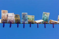 Paper Money Pegged Value. Paper fiat money currency pegged on the line blowing in the wind and fading and moving to inflation and extinction royalty free stock photography