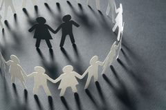 Paper figure of a couple surrounded by circle of paper people holding hands on white surface. Bulling, minorities. Paper figure of a couple surrounded by circle royalty free stock images