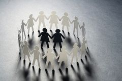 Paper figure of female couple surrounded by circle of paper people holding hands on gray surface. Bulling, minorities. Paper figure of female couple surrounded royalty free stock photography