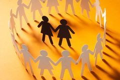 Paper figure of female couple surrounded by circle of paper people holding hands on yellow surface. Bulling, minorities. Paper figure of female couple surrounded stock image