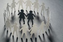 Paper figure of female couple surrounded by circle of paper people holding hands on yellow surface. Bulling, minorities. Paper figure of female couple surrounded royalty free stock image