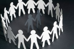 Paper figure of a male couple surrounded by circle of paper people holding hands on dark surface. Bulling, minorities. Paper figure of a male couple surrounded royalty free stock image