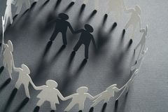 Paper figure of a male couple surrounded by circle of paper people holding hands on gray surface. Bulling, minorities. Paper figure of a male couple surrounded royalty free stock image