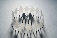 Paper figure of a male couple surrounded by circle of paper people holding hands on white surface. Bulling, minorities. Paper figure of a male couple surrounded stock photo
